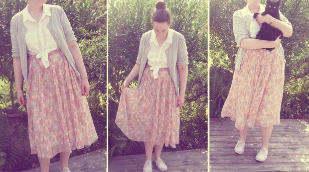 somriga kläder blommig kjol, vit knytblus, grå kofta och vita tygskor