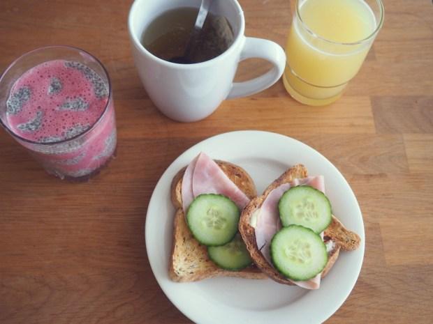 Laktosfri frukost: Glutenfria rostade bröd med smör, skinka och gurka, en kopp te, ett glas juice och laktosfri smoothie med chiapudding