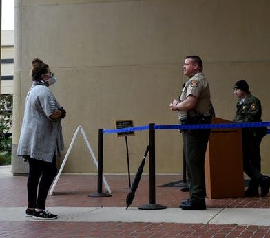 Jennifer Morrison, of Simi Valley, speaks with a Ventura County Sheriff's deputy at the entrance of Ventura County Superior Court on Friday. County law enforcement has asked the state to change bail rules due to high crime rates. (Photo/TNS)