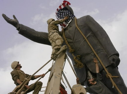 Soldiers cover a statue of Saddam Hussein with an American flag.