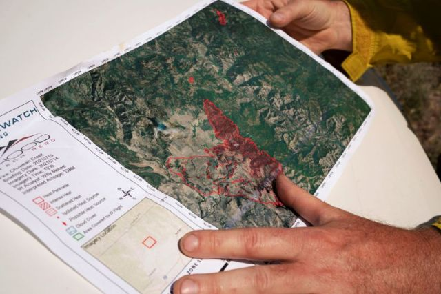 A member of the Northwest Incident Management Team 12 holds a map of the Chuweah Creek Fire as wildfires devastated Nespelem, Washington, on July 16.