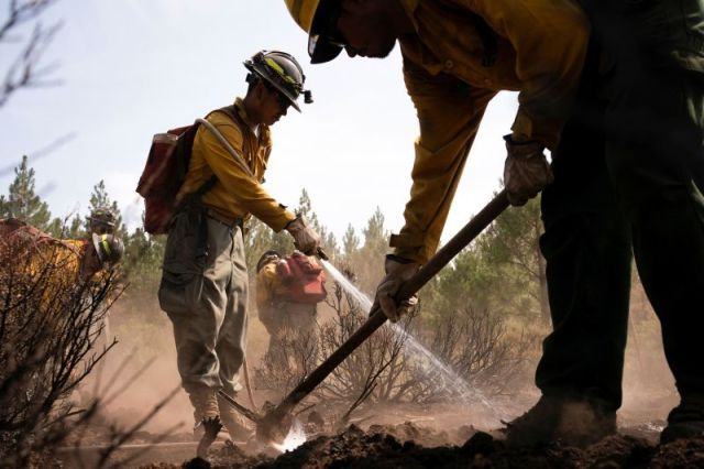 Firefighters extinguish hot spots in an area affected by the Bootleg Fire near Bly, Oregon.