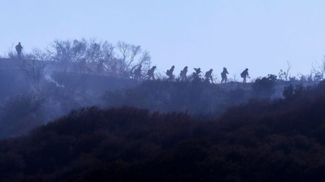 Firefighters walk near a wildfire in Topanga, California, on July 19.