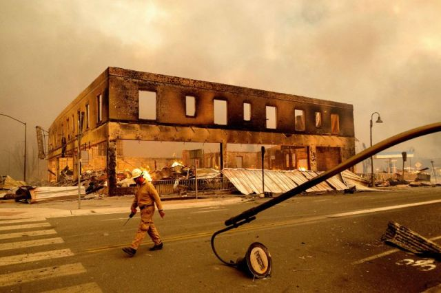 Operations Chief Jay Walter passes the historic Sierra Lodge as the Dixie Fire burns through Greenville, California, on Wednesday, August 4. The fire leveled multiple historic buildings and dozens of homes in central Greenville.