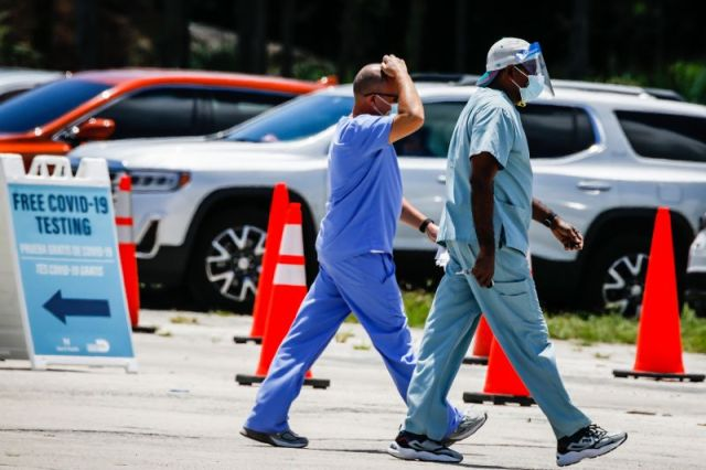 Health care workers leave following a shift at a drive-thru Covid-19 testing site at Tropical Park in Miami on Friday, August.