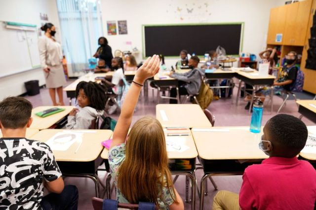 A student raises their hand in a classroom at Tussahaw Elementary School in McDonough, Georgia. Most states are leaving it up to local schools to decide whether to require masks.