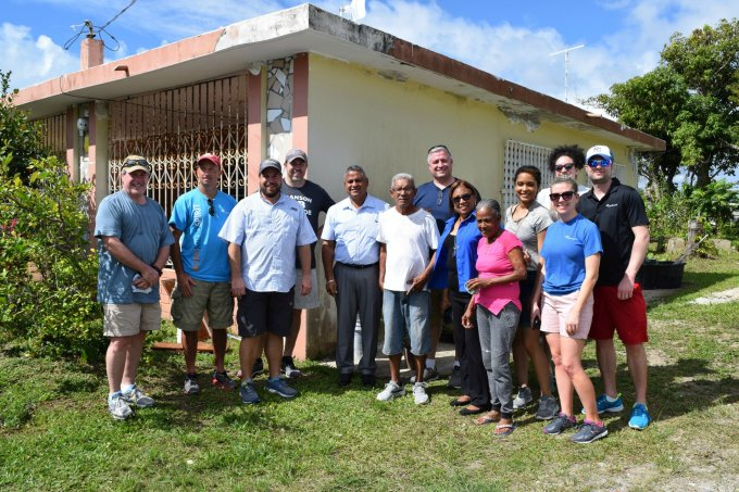 A group of leaders pose with Virginia, whose home is being renovated.