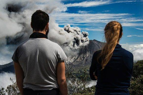 Tourists look at the ash spewed out by the Turrialba volcano in Cartago, 35 km east of San Jose, on January 6, 2017.  The Costa Rican authorities declared a green alert in the entire metropolitan area around the capital. / AFP PHOTO / Ezequiel Becerra