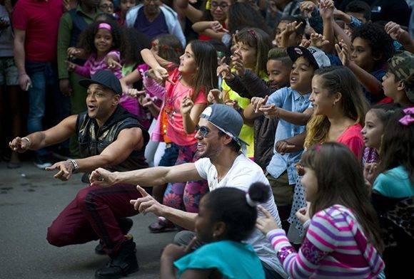 """Descemer Bueno y Enrique Iglesias con los niños del proyecto """"Paso a paso"""", en La Habana durante la realización del video """"Súbeme la radio"""", estrenado este viernes en You Tube. Foto tomada de hola.com."""