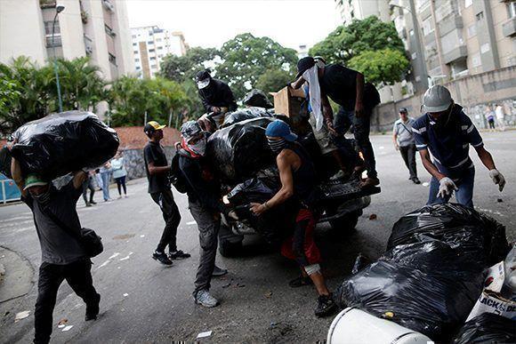 Un grupo de manifestantes construye una barricada durante una protesta contra el Gobierno de Nicolás Maduro en Caracas, Venezuela, el 26 de julio de 2017. Foto: Ueslei Marcelino/ Reuters.