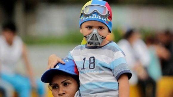 """Una madre con su hijo disfrazado de """"guarimbero"""" en una marcha convocada por la oposición. Foto: Facebook"""