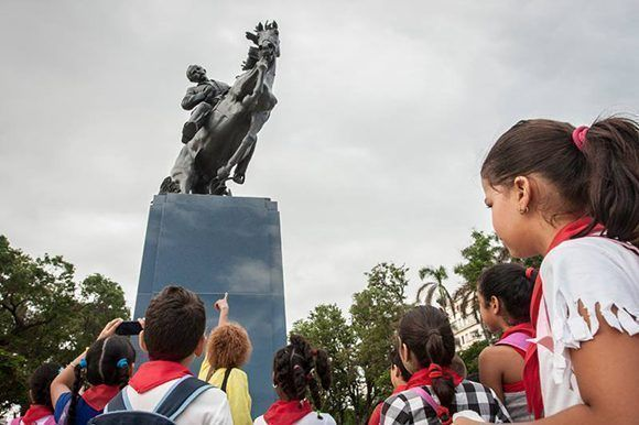Niños cubanos observan la estatua de Martí en el parque 13 de Marzo en La Habana. Foto: René Pérez Massola/ Trabajadores.
