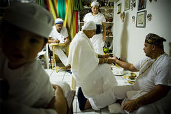 A Santería priest performs the cleansing ceremony on Nevarez (center) before 60 or so deities, which sit in pots on the shelves to her left.
