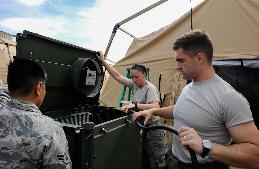 Airman 1st Class Alexa Fagaragan (left), and Airman Robyn Nelson (middle), 86th Medical Support Squadron war reserve material technicians, hook an air conditioning unit to a generator to dry out tents with Staff Sgt. Tyler Wilson (right) , 86th MDSS WRM supervisor at Ramstein Air Base, Germany, Sept. 28, 2016. The tents were used during Exercise Immediate Response 2016 in Slovenia from Sept. 9 to 23. Immediate Response 2016 was an exercise that tested a rapid response for aeromedical evacuation operations. (U.S. Air Force photo by Airman 1st Class Savannah L. Waters)