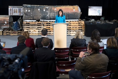 The U.S. ambassador to the United Nations stands in front of evidence during a news conference.
