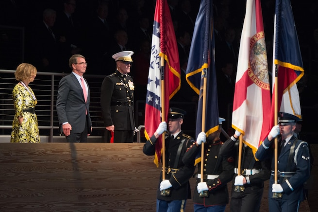 Defense Secretary Ash Carter, center, his wife, Stephanie, and Marine Corps Gen. Joe Dunford, chairman of the Joint Chiefs of Staff, stand as the U.S. Army Band passes for review during Carter's farewell ceremony at Joint Base Myer-Henderson Hall, Va., Jan. 9, 2016. DoD photo by Army Sgt. James K. McCann