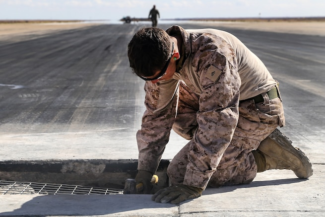 A Marine preps a pothole on a runway to be filled with concrete during maintenance at Al Asad Air Base, Iraq, March 4, 2017. Army photo by Sgt. Lisa Soy