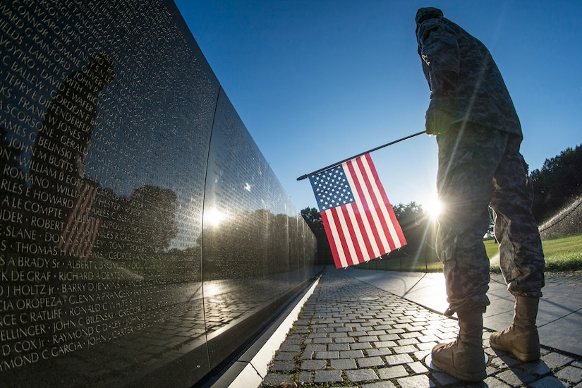 Soldier stands at Vietnam War Memorial with flag.