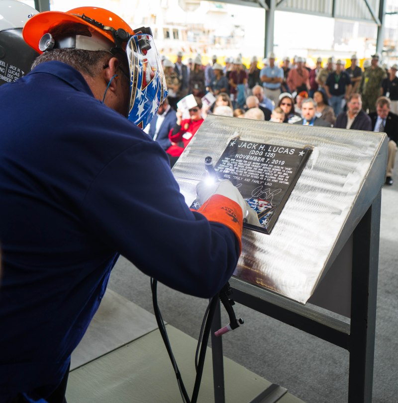 PASCAGOULA, Miss. (Nov. 7, 2019) Ingalls Shipbuilding welder James Ellis welds Ship Sponsors Ruby Lucas and Catherine B. Reynolds' initials into a steel plate during a keel authentication ceremony for the future USS Jack H. Lucas (DDG 125) at Huntington Ingalls Industries Pascagoula shipyard Nov. 7, 2019. (Photo by Samantha Crane)