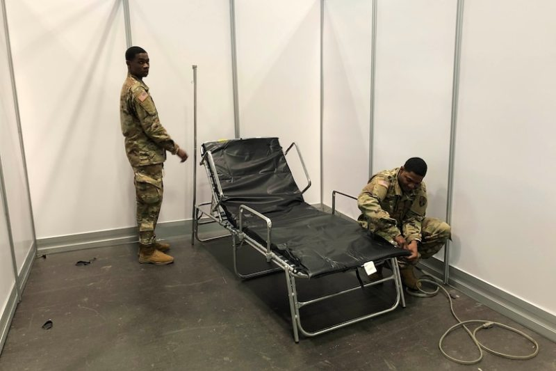 Service members set up beds for an alternate care facility at the Jacob K. Javits Convention Center in New York City, March 26, 2020. Photo By: Air Force Senior Airman Sean Madden.