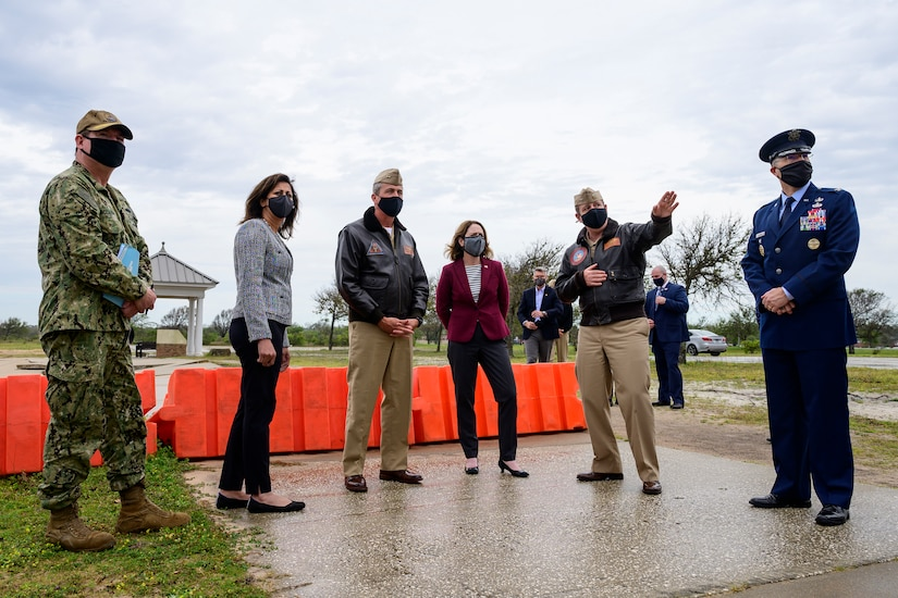 Six individuals stand outdoors on an overcast day.