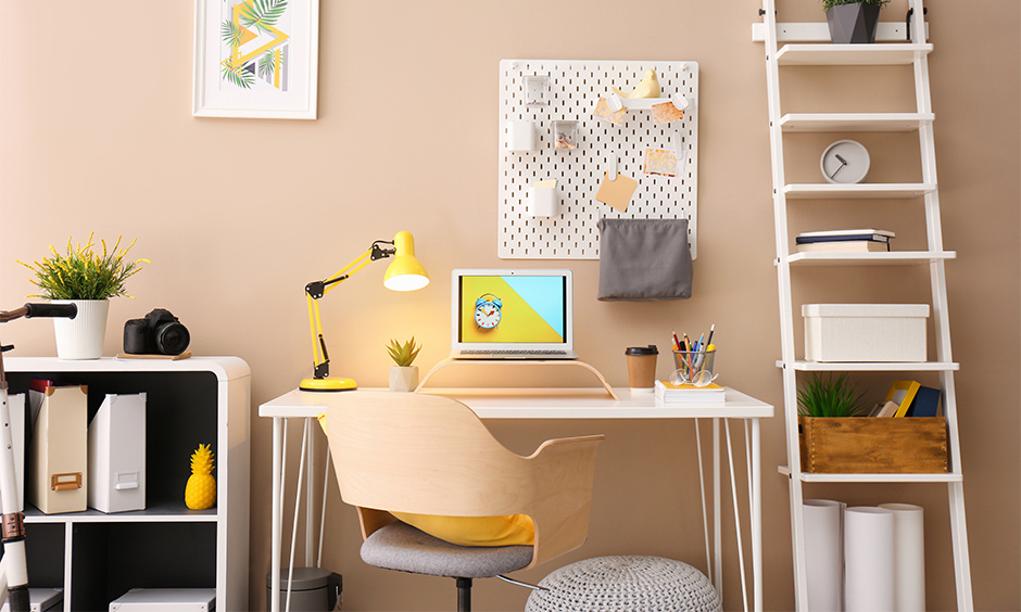 Creamy small study room decorating idea with table light, ladder shelf and notice board brings elegant look.