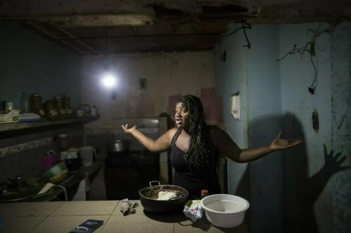 En esta imagen del 14 de febrero de 2019, Dugleidi Salcedo se queja con una vecina sobre el alto precio de los alimentos mientras prepara arepas para sus tres hijos en su cocina en el vecindario de Petare, en Caracas.
