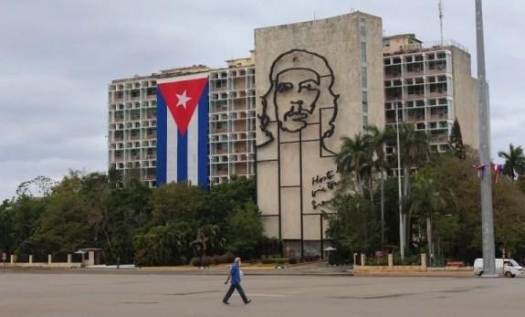 Un hombre usa una mascarilla facial mientras camina frente a un edificio gubernamental en La Habana, Cuba.