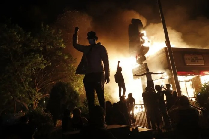 Protesters concentrated in front of a restaurant on fire in Minneapolis, Friday, may 29, 2020, during protests over the death of George Floyd, an african-american man stopped by the police.