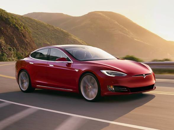 A red Tesla Model S driving in a road by the mountains