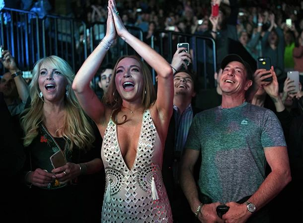 Lindsay Lohan spotted wearing a giant emerald sparkler while out with sister Ali, mom Dina and father Michael, singing DURAN DURAN tunes during their Tuesday evening concert at Barclays Center in Brooklyn, NYC.