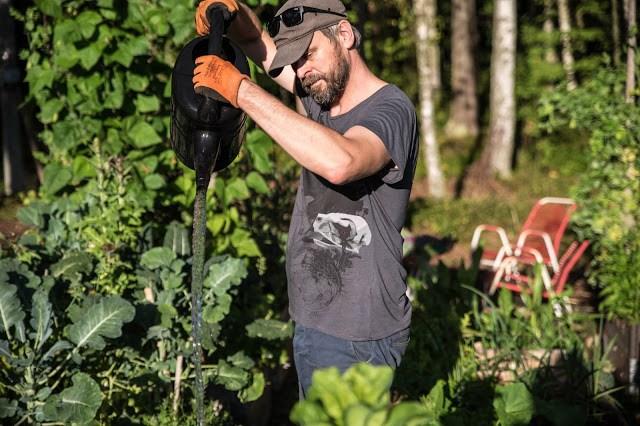 Johannes Wätterbäck vattnar i skogsträdgården Farbror Grön