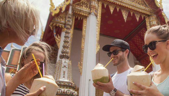 Four happy tourists drinking coconut water in Bangkok, Thailand