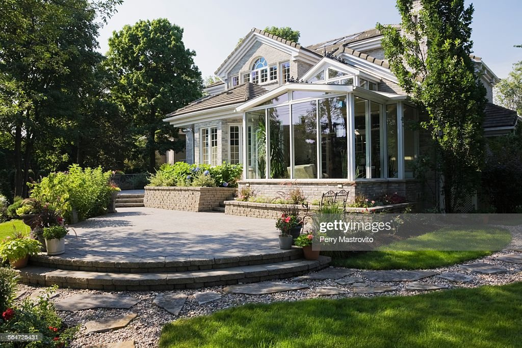 brick and stone cottage style home with sunroom patio and landscaped backyard quebec canada high res stock photo getty images