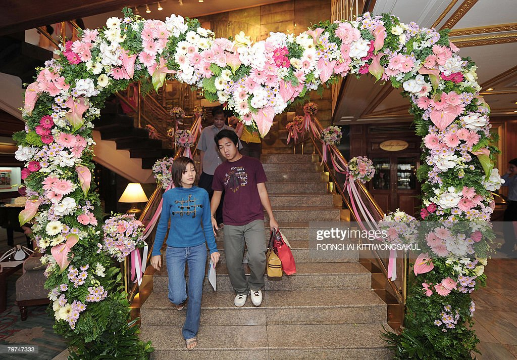 A Couple Walks Through An Entrance Gate Decorated With