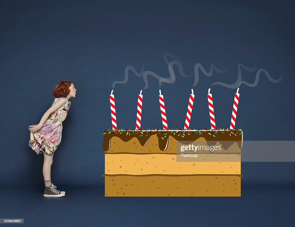 Girl Blowing Out Candles On Cartoon Birthday Cake Stock