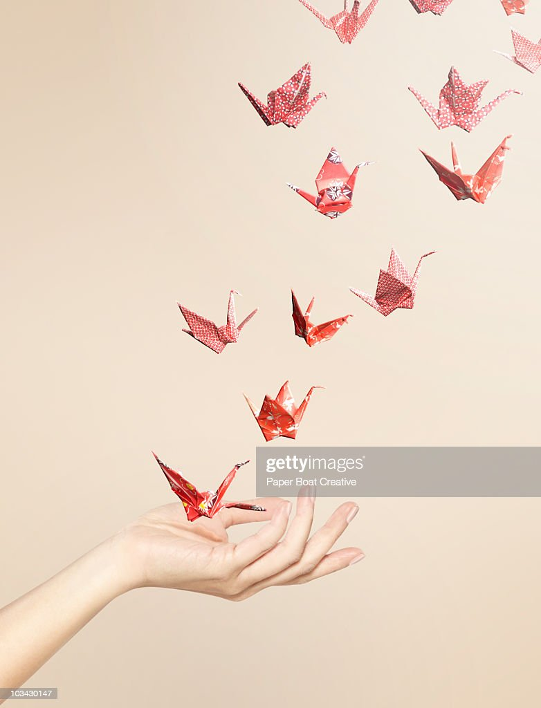 Group Of Red Origami Cranes Flying Away From Hand Stock
