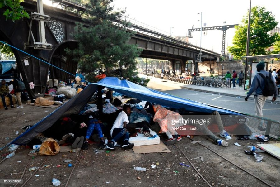Migrants and refugees rest under a tent by a railway bridge during     Migrants and refugees rest under a tent by a railway bridge during the  evacuation of a makeshift camp at Porte de la Chapelle  northern Paris  on  July 7