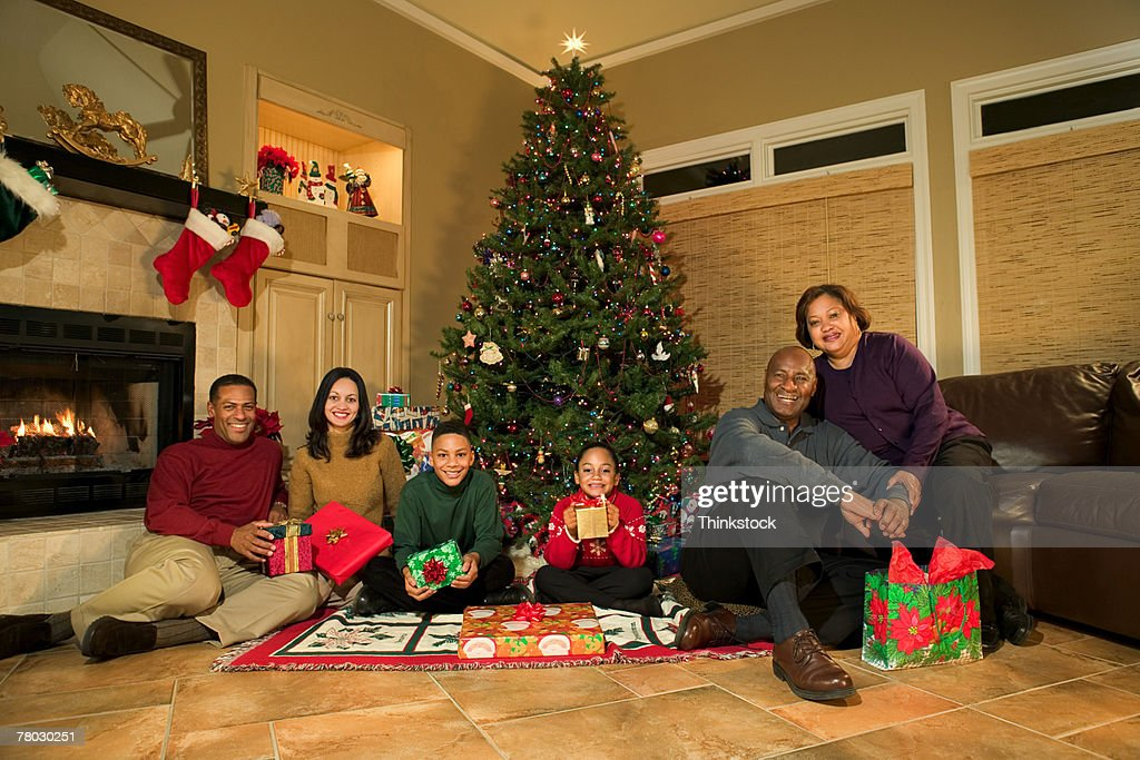 photo portrait of a family sitting around the tree on christmas day