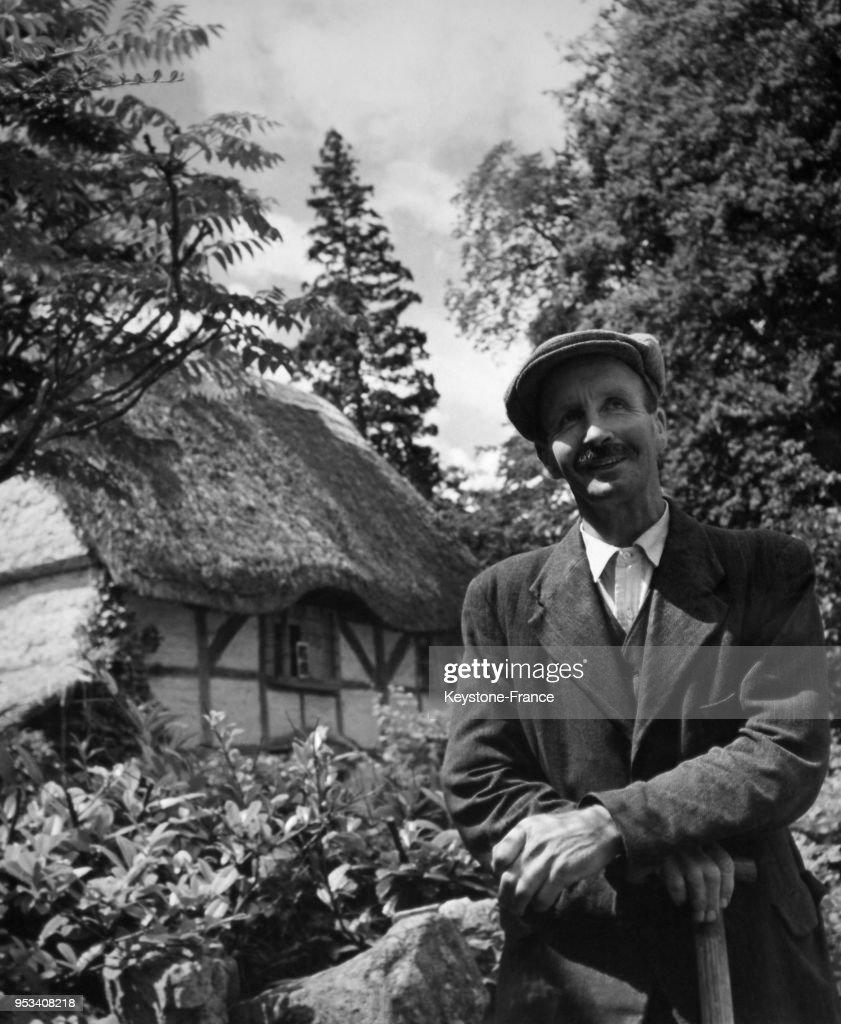 un homme devant son cottage au toit de chaume