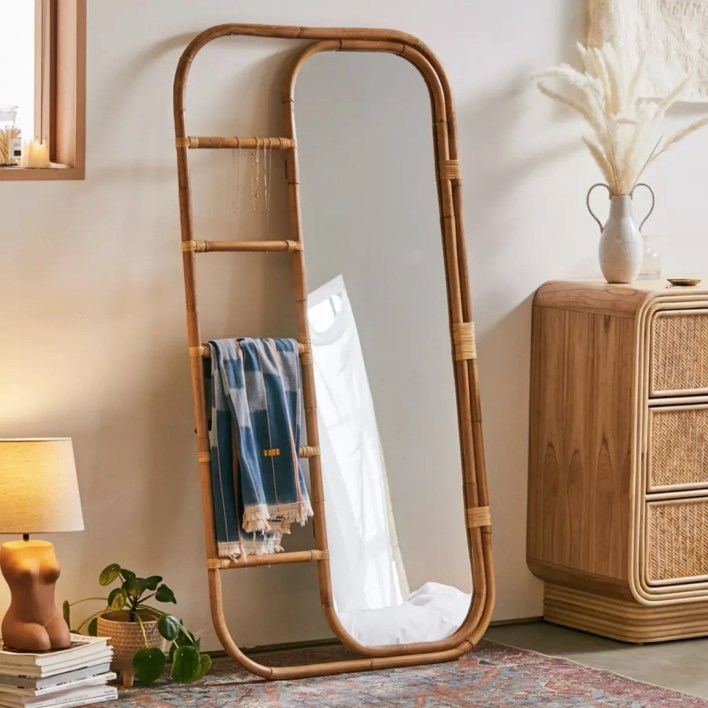 leaning rattan-framed mirror