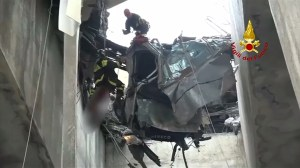 Italian fire brigade rescue person from suspended car after bridge collapse