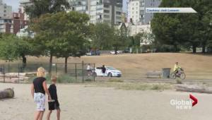 Car drives on bike path at Vancouver's Sunset Beach