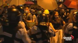Hong Kong police fire pepper spray at protesters outside police station