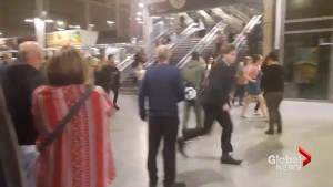 Panicked people run through train station in Manchester, England near arena where explosions heard