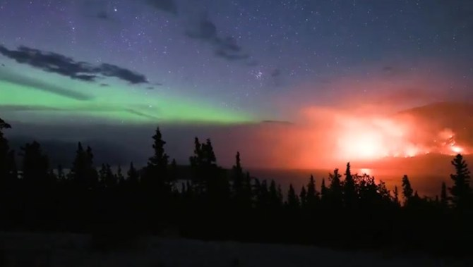 'The feeling is unreal': Wildfire burns beneath northern lights in stunning video