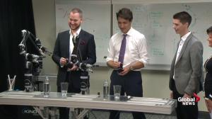 Justin Trudeau operates robotic arm, pours glass of water