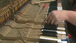 Man repairing damaged piano in Edmonton LRT pedway