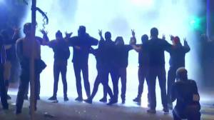G20 protesters with hands up get sprayed by police water cannon