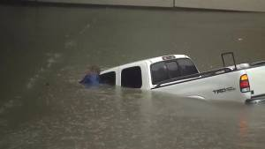 Man sticks with sunk truck drifting in flood waters in Houston